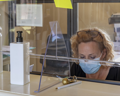 The new way of working imposed by the needs to avoid possible contagions from Covid-19 coronavirus, with plexiglass screen and mask