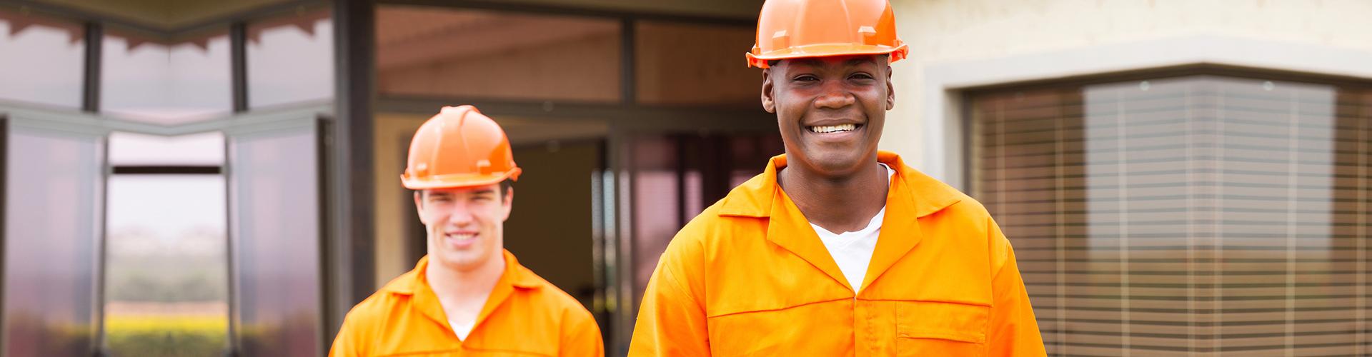 two men wearing orange hard hat and orange uniform